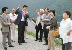 写真:5月現地調査で説明を受ける議員団